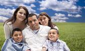 Hispanic Family Portrait Sitting in Grass Field — Stock Photo