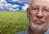 Melancholy Senior Man with Grass Field Behind — Stock Photo