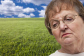 Melancholy Senior Woman with Grass Field Behind — Stock Photo