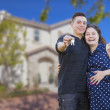 Hispanic Couple with House Keys In Front of New Home — Foto Stock