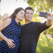 Pregnant Wife and Husband Taking Cell Phone Picture of Themselve — Stock Photo #40984663