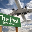 Stock Photo: The Past Green Road Sign and Airplane Above