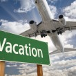 Vacation Green Road Sign and Airplane Above — Stock Photo