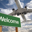 Stock Photo: Welcome Green Road Sign and Airplane Above