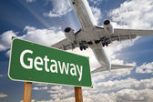 Getaway Green Road Sign and Airplane Above — Stock Photo
