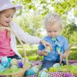 Cute Young Brother and Sister Enjoying Their Easter Eggs Outside — Stock Photo #43076283