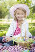 Linda chica joven con sombrero goza de sus huevos de pascua — Foto de Stock