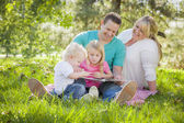 Young Family Enjoys Reading a Book in the Park — Stock Photo