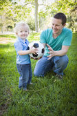 Young Boy and Dad Playing with Soccer Ball in Park — Stock fotografie
