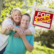 Couple In Front of Sold Real Estate Sign Holding Keys — Stock Photo