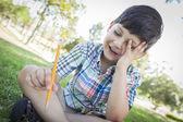 Frustrado bonito rapaz segurando o lápis, sentado na grama — Fotografia Stock
