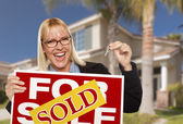 Excited Woman Holding House Keys and Sold Real Estate Sign — Stock Photo