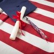 Graduation Cap and Diploma Resting on American Flag — Stock Photo #47329945
