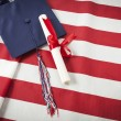 Graduation Cap and Diploma Resting on American Flag — Stock Photo #47329953