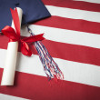 Graduation Cap and Diploma Resting on American Flag — Stock Photo #47329967