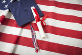 Graduation Cap and Diploma Resting on American Flag — Stock Photo