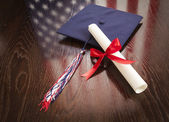 Graduation Cap and Dipoma on Table with American Flag Reflection — Stock Photo