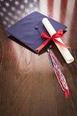 Examen mössa och dipoma på bordet med amerikanska flaggan reflektion — Stockfoto