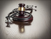 Gavel and Stethoscope on Reflective Table — Stock Photo