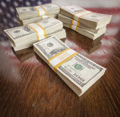 Thousands of Dollars with Reflection of American Flag on Table — Stock Photo