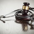 Gavel and Stethoscope on Reflective Table — Stock Photo #47651691
