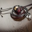 Gavel and Stethoscope on Reflective Table — Stock Photo #47651703