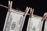 Honderd dollarbiljetten opknoping van waslijn op donkere achtergrond — Stockfoto