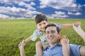 Blandras far och son spelar piggyback på gräsplan — Stockfoto