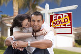 Hispanic Couple, New Home and Sold Real Estate Sign — Stock Photo