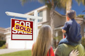 Family Facing Sold For Sale Real Estate Sign and House — Stock Photo