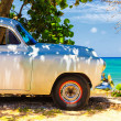 Vintage car at a beach in Cuba — Stock Photo
