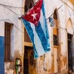 Shabby house in Old Havana with a cuban flag — Stock Photo