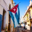 Street in Old Havana with a cuban flag — Stock Photo