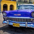 Vintage Chevrolet in front of colorful buildings in Cuba — Stock Photo