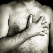 Topless man suffering a pain in his chest — Stock Photo