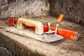 Trowels and other masonry tools on a concrete wall — Stock Photo
