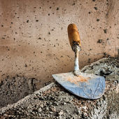 Dirty trowel above a concrete wall — Stock Photo