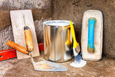 Paint can and masonry tools on a rough concrete surface — Stock Photo