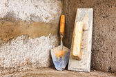 Masonry tools on a concrete wall — Stock Photo