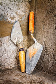 Dirty trowels on a concrete wall — Stock Photo
