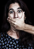 Frightened woman covering her mouth isolated on black — Stock Photo