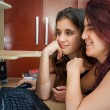 Latin mother and her daughter using a computer at home — Stock Photo