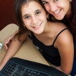 Latin girl and her beautiful mother working on a computer at hom — Stock Photo