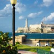 Park in Havana with the castle of El Morro in the background - Stock Photo