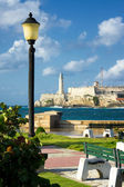 Park in Havana with the castle of El Morro in the background — Stock Photo