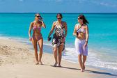 три молодых туристов, гуляющих на кубинский пляже — Стоковое фото