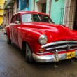 Old red car in a shabby street in Havana — Stock Photo #16184757