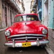 Old red car in a shabby street in Havana — Stok fotoğraf