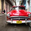 Stock Photo: Old red car in a shabby street in Havana