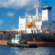Tugboat guiding a huge cargo ship — Stockfoto